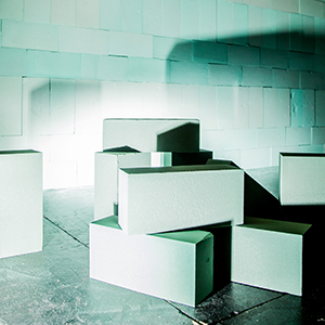 Cubes and rectangles of foam, casting shadows across a wall