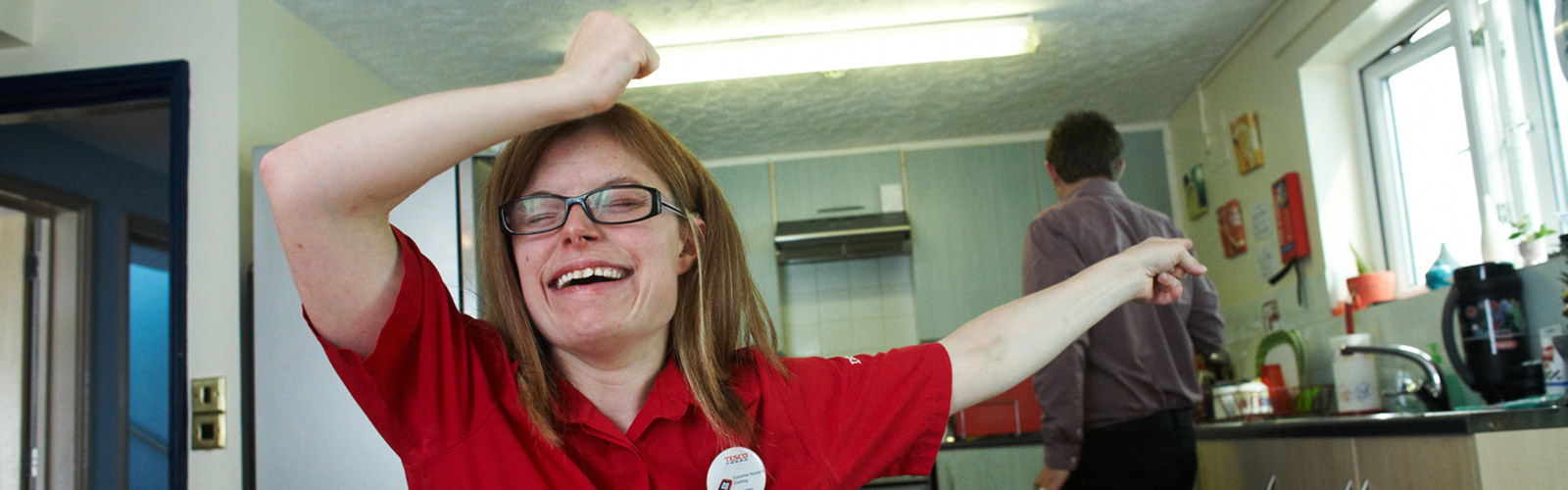 A young woman laughing with her arms in the air