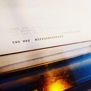 image shows a typewriter reel with the text two way mirrorrrrrrrr